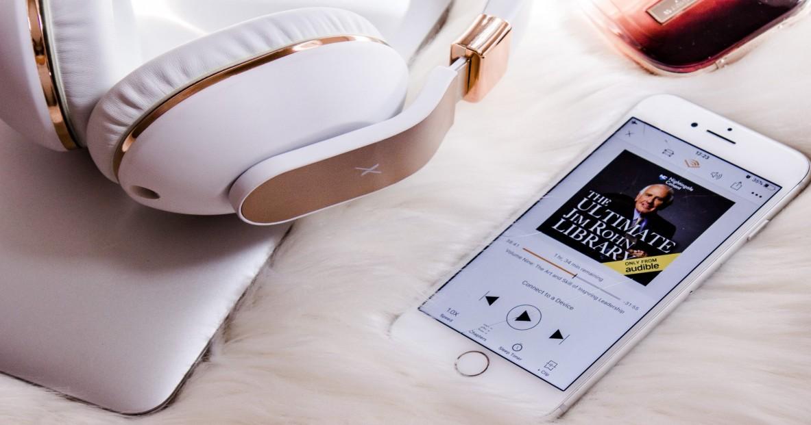 Casque audio avec un smartphone blanc jouant un livre audio