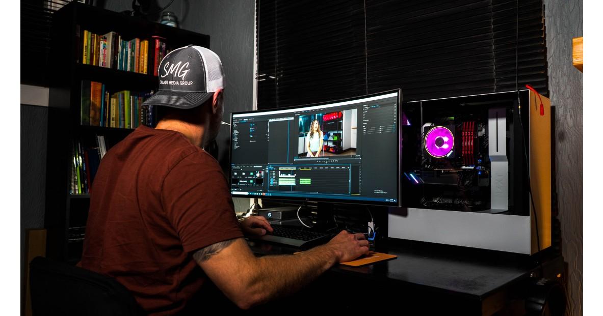Un homme avec une casquette à l'envers en train de faire de l'édition vidéo sur ordinateur