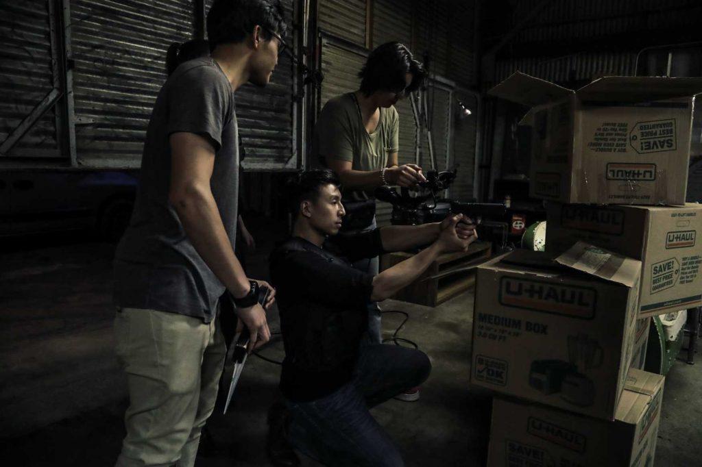 Trois hommes en plein tournage d'un film. L'un d'eux est agenouillé et tient un pistolet