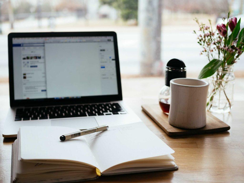 Un cahier ou vert avec un stylo et un ordinateur pour l'écriture d'un scénario