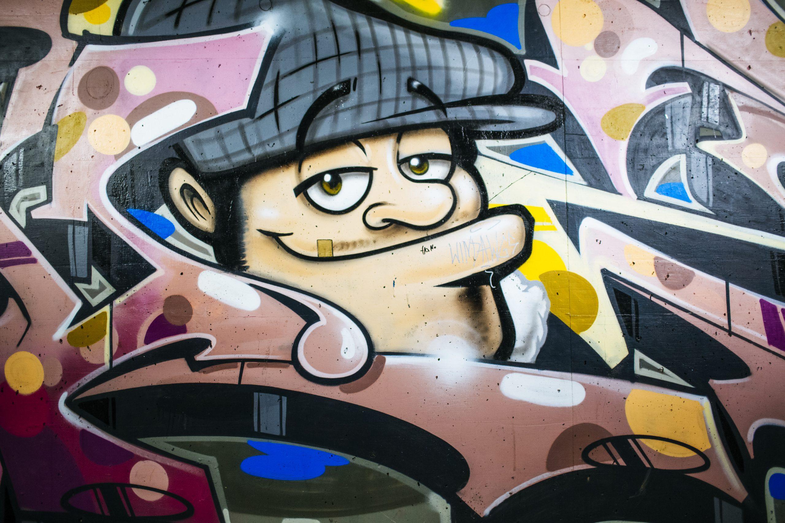 Un graffiti représentant un homme souriant portant un béret