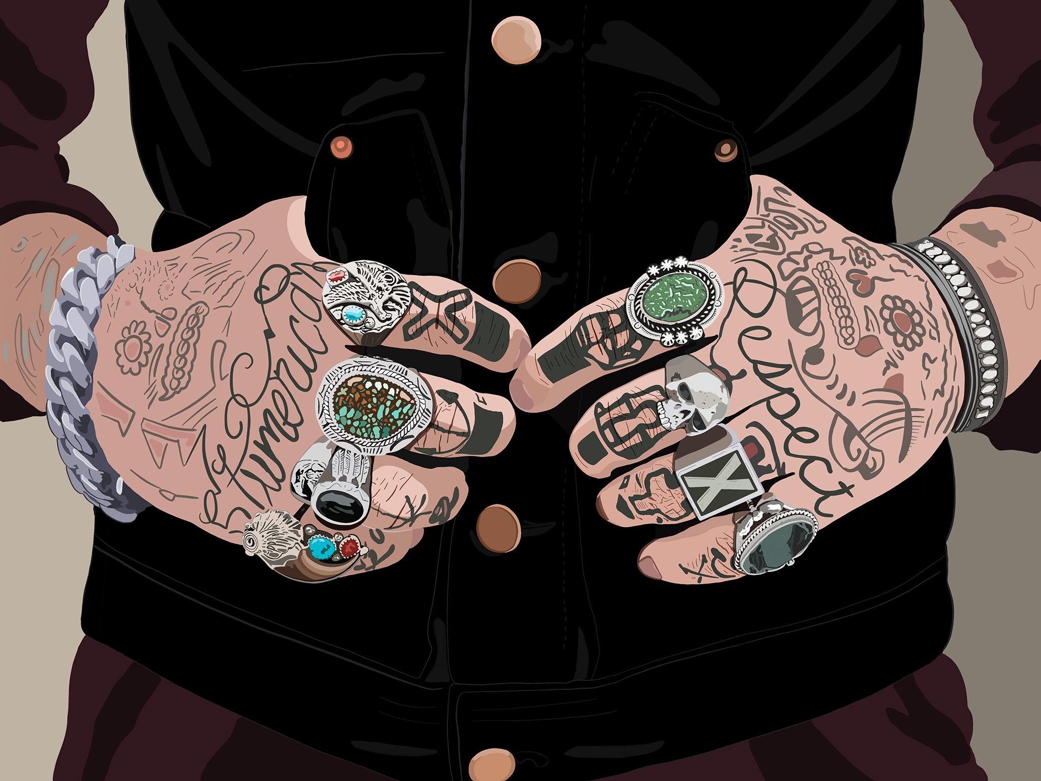 Deux mains tatouées et baguées dont les pouces rentrent dans les poches de la veste