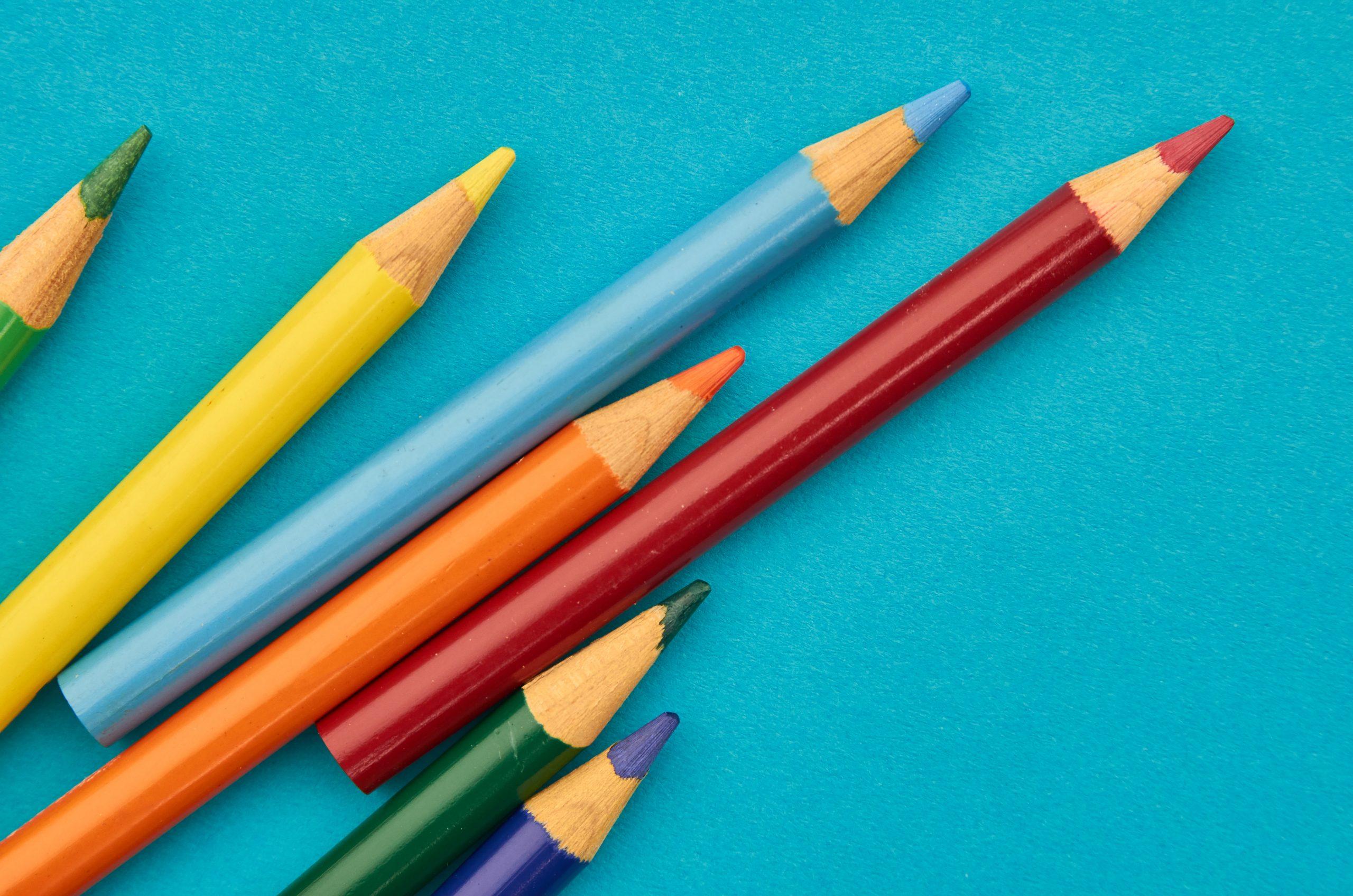 Des crayons de différentes couleurs sur un fond bleu turquoise