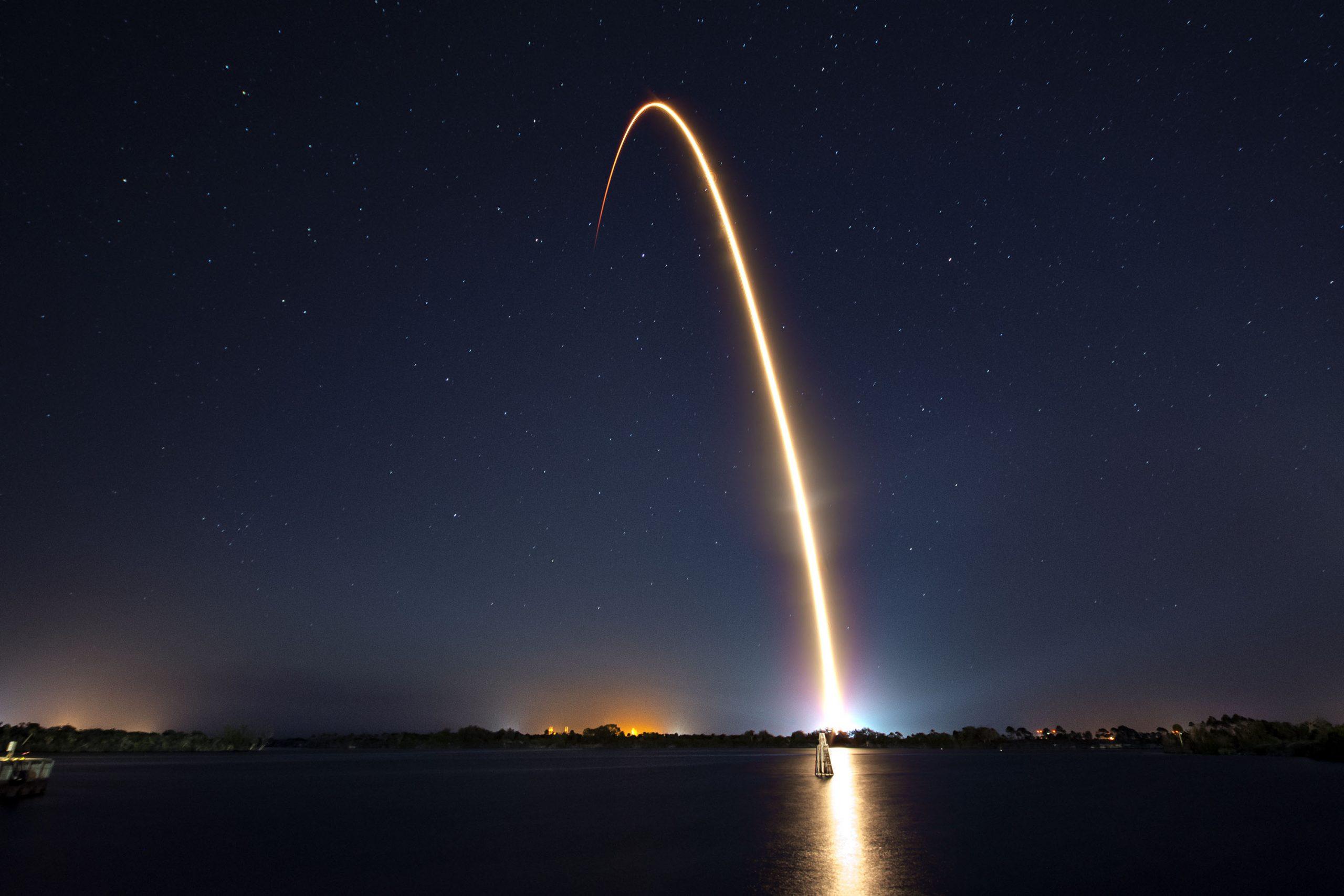 Le lancement d'une fusée SpaceX avec une trainée de lumière dans la nuit
